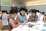 종이로 만드는 메뚜기. 엄마, 아빠와 함께 곤충 종이접기를 배우고 있는 아이들의 눈이 즐거운 호기심으로 가득 차 있다.