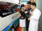 주유소 고객이 Kixx품질서비스 차량에서 품질분석원에게 시료 분석 결과를 듣고 있다.
