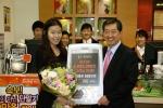 KTF 조영주 사장이 SHOW 5백만 번째 고객인 양나들 氏에게 축하꽃다발과 5백만원 상당의 무료통화권을 전달하고 있다.