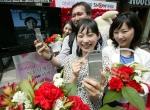 서울 명동 KTF 오렌지 갤러리 앞에서 열린 '어버이날 부모님께 SHOW 하세요' 행사에 참가한 한 고객이 508송이의 카네이션으로 장식된 포토 월 앞에서 부모님과 영상통화를 하고 있다.