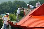 KTF 임직원들이 민통선 마을을 방문하여 장마철을 대비하여 독거노인 주택의 지붕을 방수페인트를 칠하고 있다.