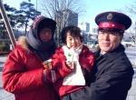 12월 15일 서울 광화문 자선냄비 앞에서 영하 10도의 날씨 속에서도 어려운 이웃을 위해 모금 운동을 하고 있는 봉사자에게 구세군 자원봉사 어린이가 화장품을 전해주고 있다.