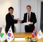 현대중공업 강영석 오슬로 지사장(사진 오른쪽)과 회그LNG사 사업 총책임자 베가르 헬레클레이브(VAGARD HELLEKLEIV)가 계약 서명 후 악수하고 있다.