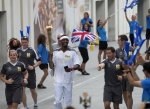영국 삼성전자 올림픽 홍보대사인 필립스 이도우(Phillips Idowu, 세단뛰기 영국 국가대표)가 런던 스트라트포드(London, Stratford) 웨스트필드(Westfield)에서 성화를 들고 뛰고 있다. (사진제공: 삼성전자)