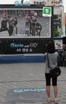 지난 5월 대전 은행동에서 진행했던 '지니 AR영상쇼'에 참가한 고객이 증강현실 속의 엑소케이(EXO-K)와 포즈를 취하고 있다. (사진제공: KT)