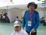 육상경기장 안내소에서 만난 1:1봉사자 김종환씨가  서울특별시 선수단의 김민석 선수(육상의 던지기-원반, 포환, 창)를 도와주고 있다.