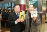이승재 서울지방우정청장(왼쪽)이 서울중앙우체국에서 첫 번째로 '싸이, 나만의 우표'를 구입한 고객에게 싸이 친필이 담긴 아트카드와 흠뻑쇼 DVD를 증정하고 기념촬영을 하고 있다.