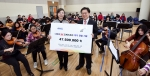 한국암웨이가 다문화 M오케스트라의 연습실을 찾아 악기 기금을 전달하고, 기념 촬영을 하고 있다. (좌측부터 다문화 M오케스트라 김유정 단장, 한국암웨이 노원호 상무)