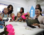 SK텔레콤은 15일 부처님오신날을 맞이해 조계사와 공동으로 동자승들을 위한 미래형 정보기술 체험관 T.um(티움) 특별 체험 행사를 개최했다. 동자승들이 스마트폰과 터치스크린을 이용해 디지털 인경 체험을 하고 있다.