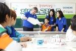 한국지멘스가 26일 구로구에 위치한 다문화 대안초등학교 지구촌학교에서 환경문제의 중요성을 알리고 친환경과학 교육을 제공하는 '지멘스그린스쿨'을 진행했다. 참가 어린이들이 지멘스 임직원과 대학생 서포터즈의 도움을 받아 친환경 에너지 실험을 하고 있다.