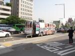컨닝앱 랩핑 버스를 시민이 찍고 있다.