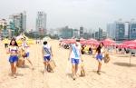 듀렉스 관계자, 서포터즈들이 광안리 바닷가에서 해변을 청소하며 안전수칙을 알리고 있다.