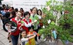 9월 18일 무교동 어린이재단 본부 앞 광장에서 진행된 테팔, 사랑나눔 바자회에서 팽경인 테팔 대표 및 직원들과 이충로 초록우산 어린이 재단 본부장이 결식아동들을 위한 응원의 메시지를 희망트리에 달고 있다.