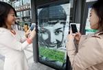 버스 정류장에서 버스를 기다리는 사람들이 오드리 헵번, 뷰티 비욘드 뷰티 전시회 버스 쉘터 광고 속 오드리 헵번 사진을 찍는 모습