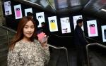 서울시 지하철 신촌역 내에서 LG전자 모델이 '아카'를 손에 들고 포즈를 취하고 있다. 모델 뒤에는 일반인들이 지나가고 있다. 벽에는 '아카' 디지털포스터광고가 설치되어 있는 모습