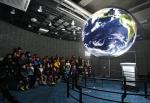 情 나눔 우주과학 캠프에 참가한 아동복지시설 청소년이 SOS에 투사된 지구를 유심히 바라보고 있다(장소: 국립고흥청소년우주체험센터 SOS실)
