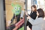 서울 신논현역 버스 정류장에서 버스를 기다리는 사람들이 내츄럴엔도텍 웰뮨 광고 인증샷 이벤트에 참여하기 위해 광고 사진을 찍는 모습.