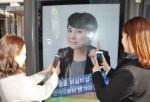 서울 신논현역 버스 정류장에서 버스를 기다리는 사람들이 내츄럴엔도텍 웰뮨 광고 인증샷 이벤트에 참여하기 위해 광고 사진을 찍는 모습