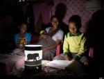 태양광 랜턴을 이용하여 책을 읽고 있는 어린이들