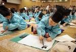 어린이들이 부모들이 지켜보는 가운데, 김봉곤 훈장의 가르침에 따라 효에 대해 배운 후 부자유친을 서예로 직접 써보고 있다.