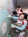 기아차 임직원들이 서울 서초구 잠원동 경부고속도로 횡단지하보도에 야광벽화를 그리고 있는 모습