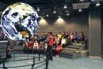 우주과학 캠프에 참가한 청소년이 SOS에 투영된 지구를 흥미롭게 바라보고 있다
