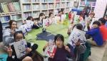 희망이음 학습지 무상지원 사업을 통해 초등학교 2학기 중간시험 대비 핸디북을 지원 받은 지역아동복지센터 나무를심는학교 학생들이 교재를 들고 기념사진을 촬영하고 있다