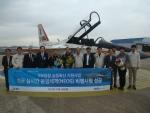 16일 사천공항에서 항공 실시간 운영체제의 네오스 비행시험에 성공한 후 한국항공우주산업과 MDS테크놀로지 관계자, 대한민국 공군 조종사들이 기념촬영을 하고 있다. 항공기는 FA-50 시제기로 개조한 T-50 훈련기