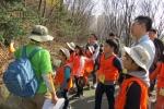 봉사활동에 참가한 한화생명 임직원이 아이들과 함께 나무에 대한 설명을 듣고 있다