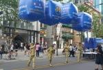 석고마임 퍼포머들이 어깨에 대회 홍보 대형 에드벌룬을 매달고 거리에서 포즈를 취하고 있다