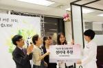 KMI 여성직원들이 저소득 청소년에게 생리대 후원을 밝히며 기부 종을 울리고 있다