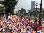 보육교사가 아이들을 보호하듯 정부도 보육교사를 보호하라는 의미로 우산시위를 하고 있는 보육교직원들의 모습