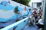 완성된 벽화를 기뻐하며 화이팅 포즈를 취하고 있는 삼성카드 임직원 봉사단