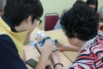 도봉노인종합복지관 어르신이 효문중학교 청소년에게 스마트폰을 배우고 있다