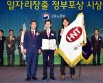 김진환 하나투어 관리본부장(가운데)이 일자리창출 유공 대통령표창을 받은 후 이기권 고용노동부 장관(왼쪽)과 함께 기념사진을 찍고 있다