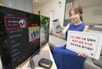 KT 홍보 모델이 올레 tv에서 비스트 홍콩 콘서트를 예약 구매할 수 있는 화면을 소개하고 있다