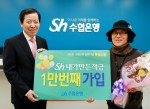 이원태 Sh수협은행장(왼쪽)이 16일 서울 송파구에 소재한 가락시장역지점에서 Sh내가만든적금 1만번째 가입 고객에게 사은품을 증정하고 기념촬영을 하고 있다