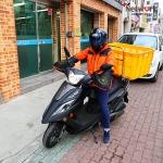 오토바이를 타고 있는 무료급식소 봉사자