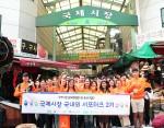 국제시장 국내외 서포터즈가 외국인 관광객 투어를 마치고 단체 사진을 촬영하고 있다