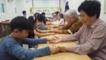 삼전종합사회복지관 이룸마을학교 아이들이 마을 어르신들에게 손마사지를 하고 있다