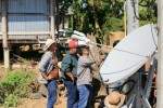 Engineers installing a satellite antenna in a rural location in Thailand