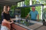 방문객이 LG 에코시티 정원 내 프리미엄 빌트인 시그니처 키친 스위트 제품들을 활용해 꾸며진 친환경 주방공간에서 냉장고를 체험하고 있다