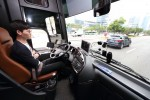 KT 자율주행 버스 운전자가 영동대로를 주행하는 도중 양손이 자유로운 상황에서 기념 촬영을 하고 있다