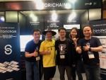 (왼쪽부터)경호연 책임 개발자, Brock Pierce, 이준수 대표, 황인주 본부장, Mickey Choi가 스토리체인 부스에서 함께 사진을 찍고 있다
