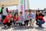 미아방지 목걸이 달아주기 캠페인에 참가한 가족이 기념사진을 찍고 있다