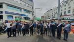 도로교통공단 서울지부 임직원들이 소상공인 이륜자동차 운전자들에게 안전 헬멧을 전달하고 기념촬영을 하고 있다