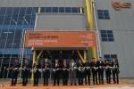 한국이구스 송도 준공식에서 인천 경제 자유구역 청장과 이구스 직원들이 테이프를 자르고 있다