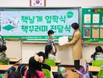 화성시문화재단 전미경 도서관장이 2020년 동탄중앙초등학교 1학년 입학생에게 책꾸러미를 전달하고 있다