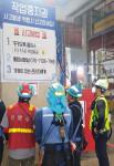 근로자들이 근로자 작업 중지권에 대한 안내문을 보고 있다