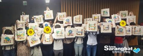 함께하는 사랑밭과 블라인드 봉사단이 함께 만든 완성된 책가방과 컬러비즈를 보여주고 있다